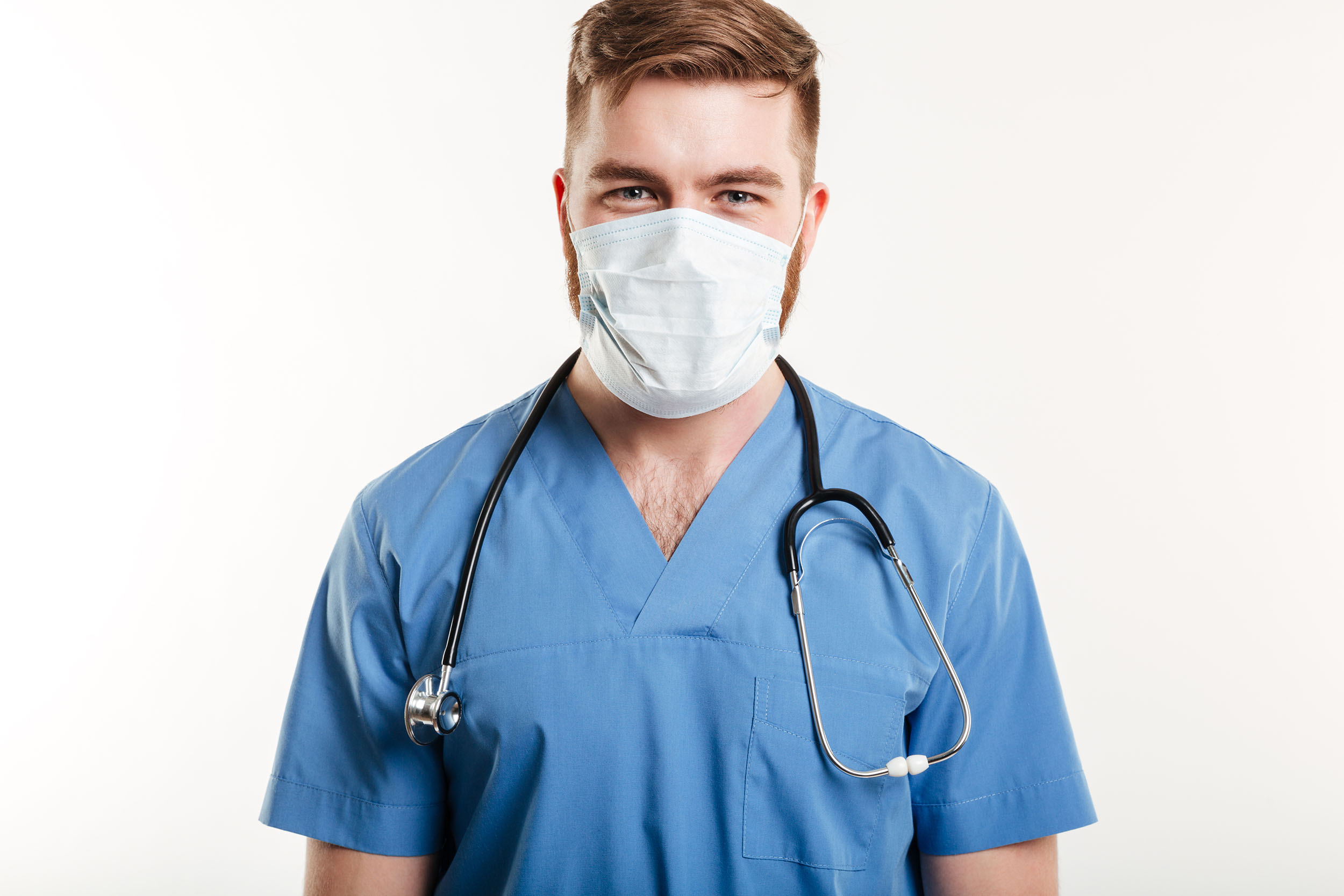 Portrait of a male surgeon wearing stethoscope and mask isolated on white background